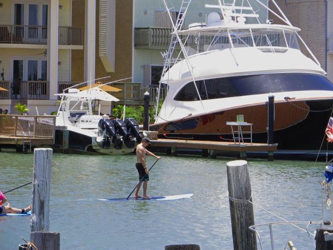 man paddling in channel by huge boat