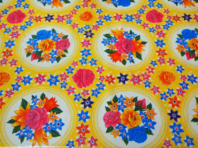 Yellow Oil cloth with flowers in cirlces.